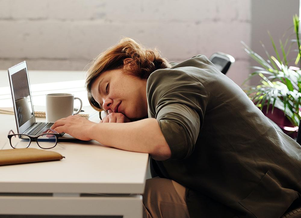 Woman with head on desk sleeping